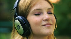 Lovely girl listening music and sending kiss to the camera, steadycam shot Stock Footage