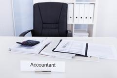 Accountant name plate on desk with empty chair Stock Photos