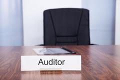 Nameplate with auditor title kept on desk in front of empty chair Stock Photos