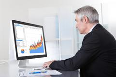 mature businessman looking at computer - stock photo