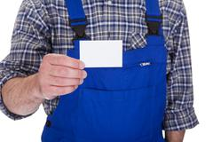mature male technician holding visiting card - stock photo