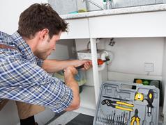 Plumber fixing sink in kitchen Stock Photos