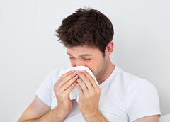 Man sneezing into a tissue Stock Photos