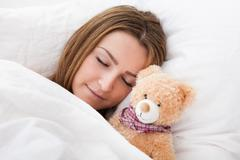 young beautiful woman sleeping on bed with her teddy bear - stock photo