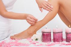 beautician waxing a woman's leg - stock photo