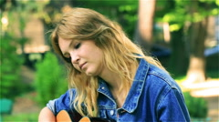 Sad girl sitting in the park and playing on the guitar, steadycam shot Stock Footage