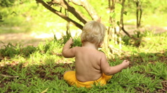 Baby sitting on grass and digging in ground Stock Footage