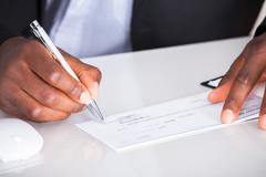 Human hand writing on cheque Kuvituskuvat