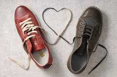 A man's shoe and a woman's shoe with laces tied together in a heart shape Stock Photos