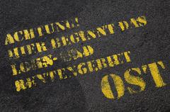 Close-up of German text on paved road (Attention, Here begins the area of wage - stock photo