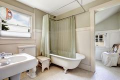 claw foot tub with light green wraparound curtain. - stock photo
