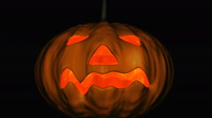 A pumpkin on a black background with a candle flashing inside Stock Footage