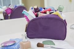 Women's toiletry and cosmetic travel bag on bathroom counter, filled with Stock Photos