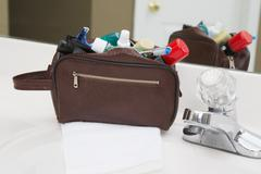 Men's toiletry travel bag on bathroom counter, filled with toothbrush, shaving Stock Photos