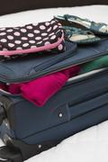 Women's toiletry travel bag on top of packed suitcase, USA - stock photo