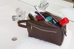 Men's Toiletry Travel Bag on Bathroom Counter filled with Personal Hygiene Stock Photos