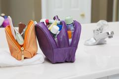 Women's Toiletry Travel Bag on Bathroom Counter filled with Personal Hygiene Stock Photos