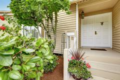 Neat entrance porch with white door and flower pot on stairs Stock Photos