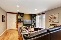 Family room with large leather couch and tv Stock Photos