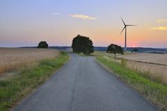 Countryside with Forked Road and Wind Turbine at Dusk, Bad Mergentheim, - stock photo