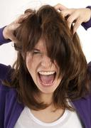 Close-up portrait of young woman screaming and looking at camera with hands in Stock Photos