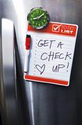 Close-up of Front of Stainless Steel Refridgerator with Magnetized To Do List Stock Photos