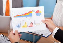 Businesspeople analyzing graph Stock Photos