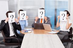 businesspeople holding question mark sign - stock photo