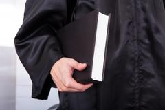 Male judge holding law book Stock Photos