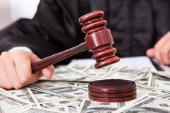 Stock Photo of judge hitting mallet on dollar