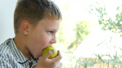 Boy Eating Apple And Looking At The Window Stock Footage