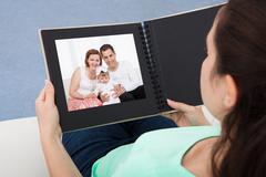 woman looking at photo album - stock photo