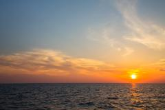 sunset on the ocean with horizon for an atmospheric background. - stock photo