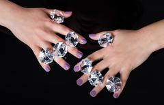 Close-up of woman's hand and diamonds isolated on black background Stock Photos