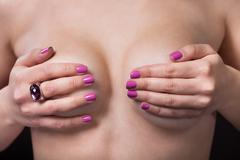 portrait of young topless woman covering her breast - stock photo