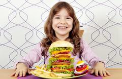 Happy little girl with big hamburger Stock Photos