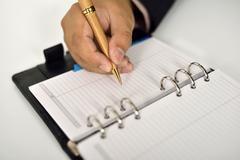 Business man writing on agenda Stock Photos