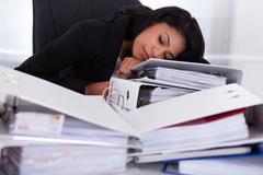 Businesswoman sleeping on piles of folders Stock Photos
