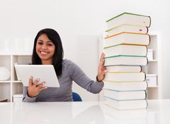 woman avoiding books and using tablet - stock photo