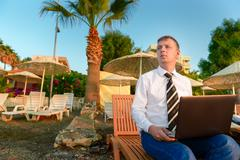 Manager in a shirt and tie on the beach on a sun lounge Stock Photos