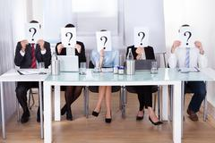 Businesspeople holding question mark in front of face Stock Photos