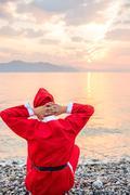 santa claus greets the sunrise over the sea - stock photo