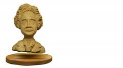 Stock Video Footage of Plasticine Einstein bust levitates above the stand.