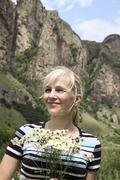 Portrait of happy woman with camomiles on a background mountains Stock Photos