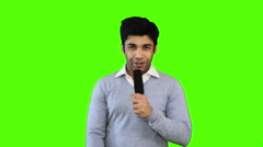 Stock Video Footage of Locked-on shot of male TV reporter talking into a microphone on green background