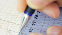 Person measuring accurate on the graph paper, using ruler and pencil, blue toned Stock Footage