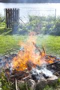 garbage in fire, illegal garden burning out. - stock photo