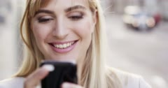 Attractive blonde business woman using smartphone laughing in city london Arkistovideo