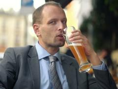 Young businessman drinking cold beer in outdoor bar NTSC Stock Footage