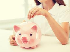 smiling child putting coin into big piggy bank - stock photo
